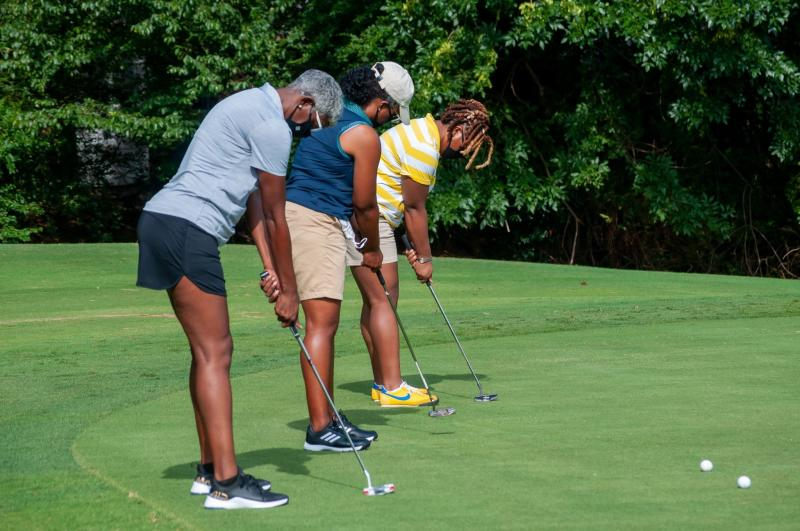 Three golfers practice their puts with an instructor at an Irving golf course.