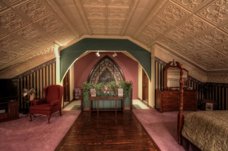 Upper room of 19th century church turned into a B&B with pink carpeting and molded ceiling.