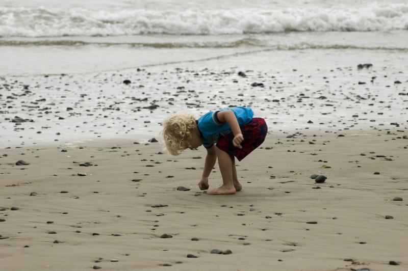 Child beachcombing on the Oregon Coast by Robert Petit