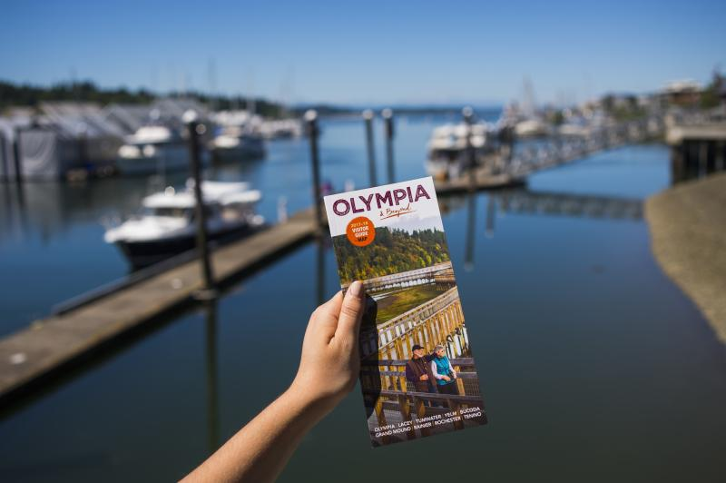 A photo of a hand holding a visitor guide looking out over Percival Landing