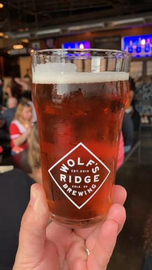Hand holding glass of Oktoberfest beer from Wolf's Ridge Brewing, glass printed with logo