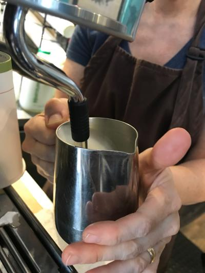 Close-up of barista's hands holding mug at coffee machine