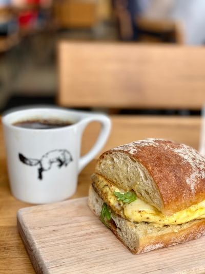 Egg sandwich on wooden cutting board and mug of coffee with fox logo from Fox in the Snow