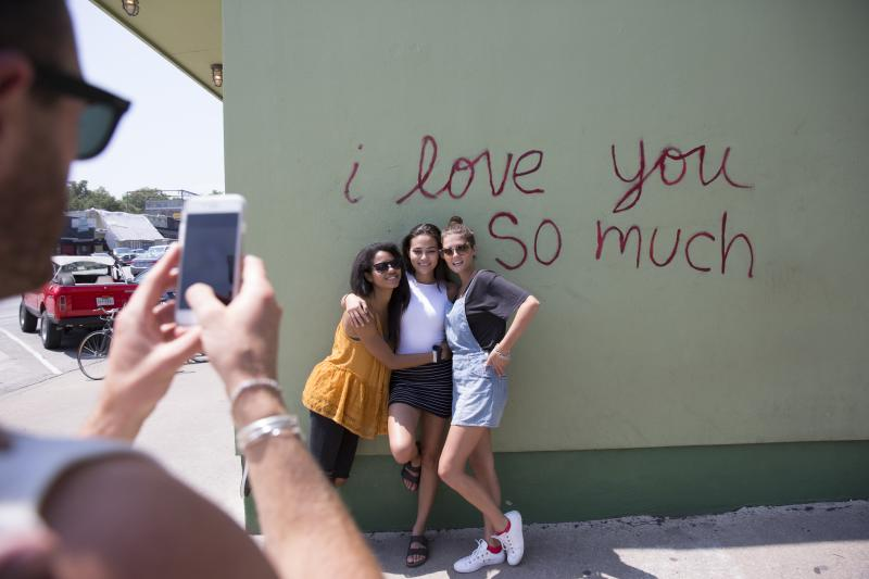 Girls posing at I Love You So Much Mural while friend takes photo