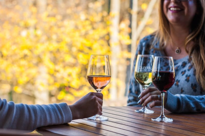 Friends enjoy glasses of wine at Oliver Winery in Bloomington, IN