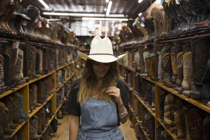 woman wearing cowboy hat in front of rows of boots