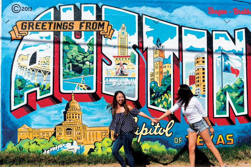 Jane Ko and friend posing at Greetings from Austin mural at Roadhouse Relics