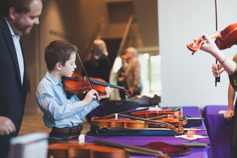 Child playing violin at Austin Symphony's summer concert series in the park at the Long Center in Austin Texas