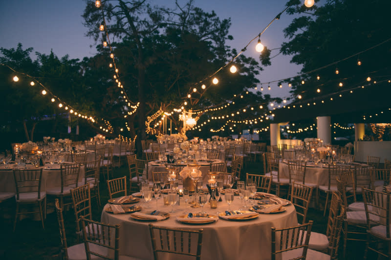 Lights illuminate an outdoor wedding reception at Oak Creek Golf Club in Irvine, CA