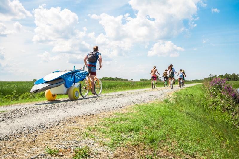 Visitors cycle down a gravel bike path in Sandbridge near Virginia Beach.