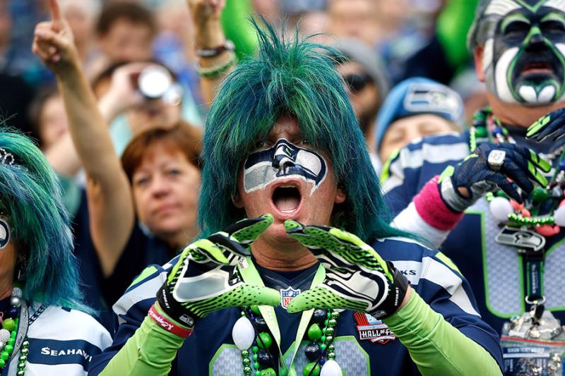Seahawk fan with face paint and wig throwing up hand signal