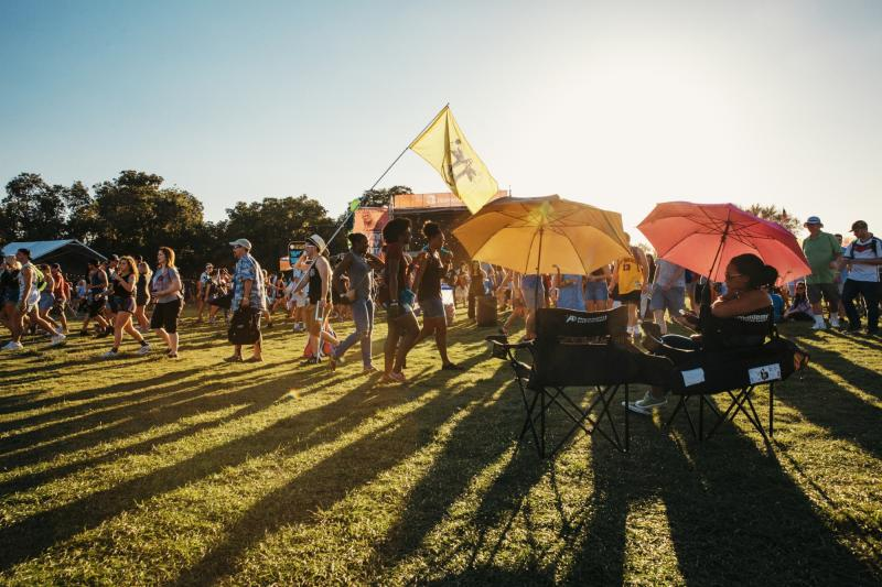 people in lawn chairs with umbrellas while crowd passes stage at ACL music festival in austin texas