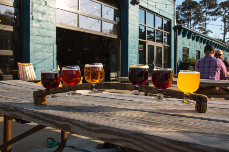 A sample of drinks are served on a picnic table outside at Commonwealth Brewing Company.