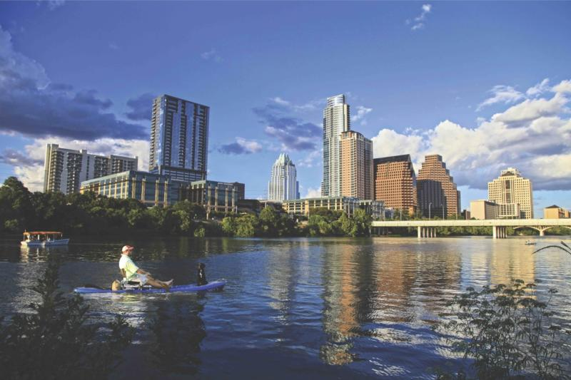 downtown austin texcas Skyline with man in kayak with dog