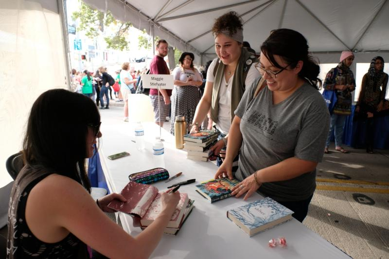 Women getting books signed by author inside tent at Texas Book Festival in austin texas