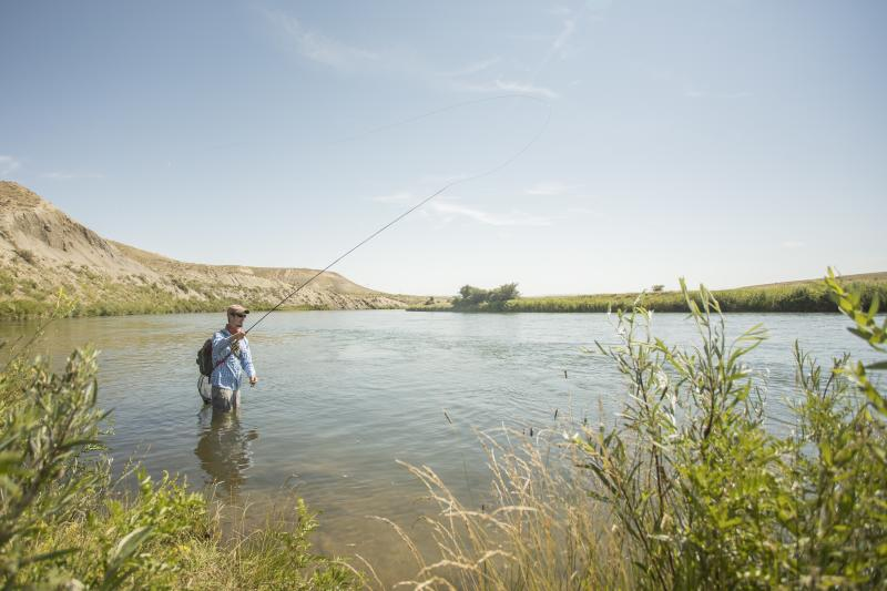 An angler casts his rod in the cool waters of the North Platte River.