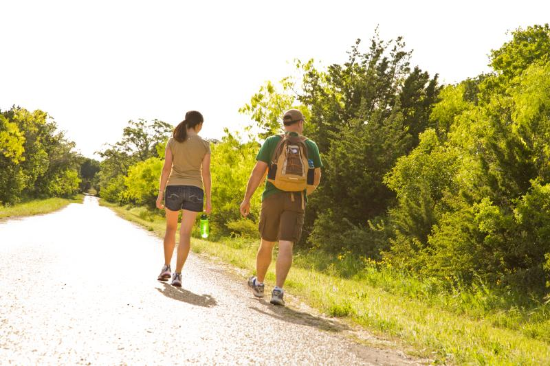A man and woman hiking along a tree lined trail in Fredericksburg, TX