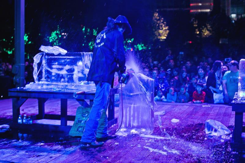 A man uses a chain saw to create an ice sculpture during Frostival at Discovery Green