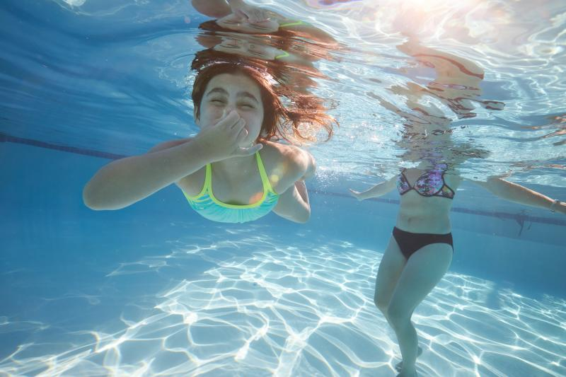 A child holds her breath under water in a large swimming pool. Her mom is behind her wading in.