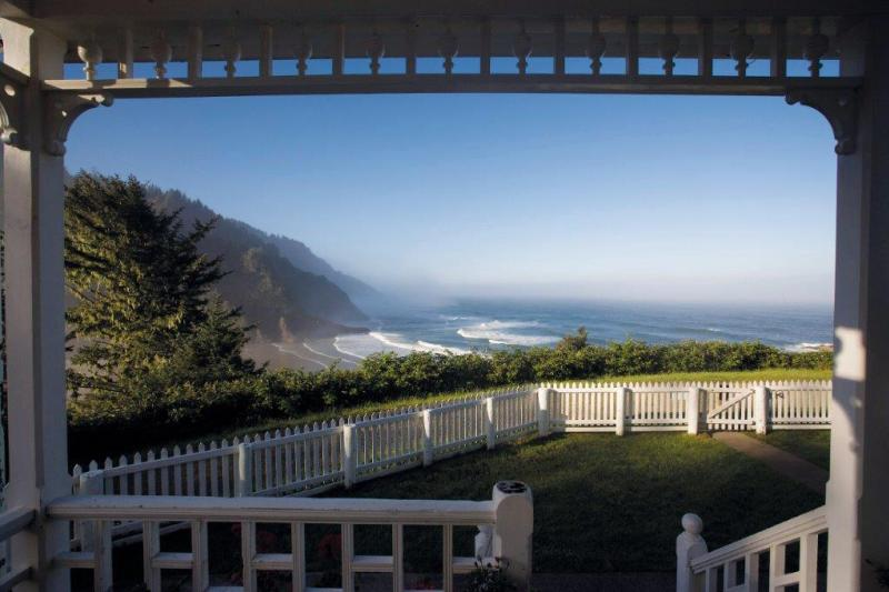 Heceta Head Lighthouse Bed & Breakfast view shows a yard with white picket fence and coastal cliffs touching the Pacific