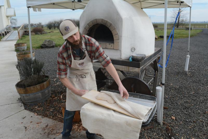 Bearded man in a flannel shirt and an apron pulling pizza dough from under a cloth. He stands in front of an outdoor pizza oven at Camas Country Mill.