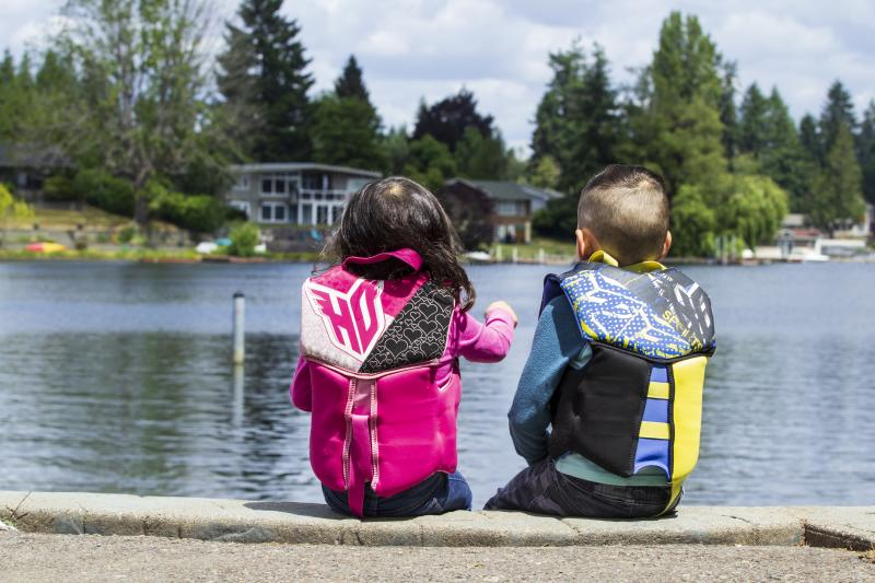 Bundled safely in life-jackets, two children enjoy the view from a dock at Long Lake Park.