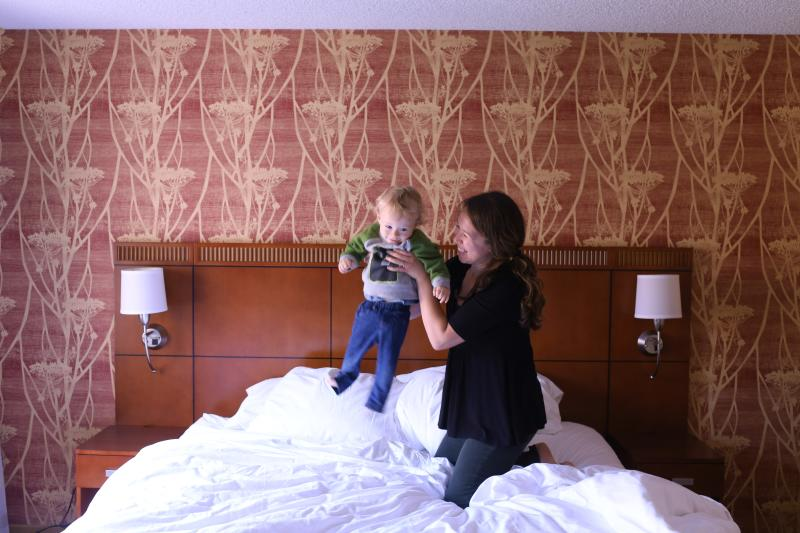 mom and baby on bed in hotel room