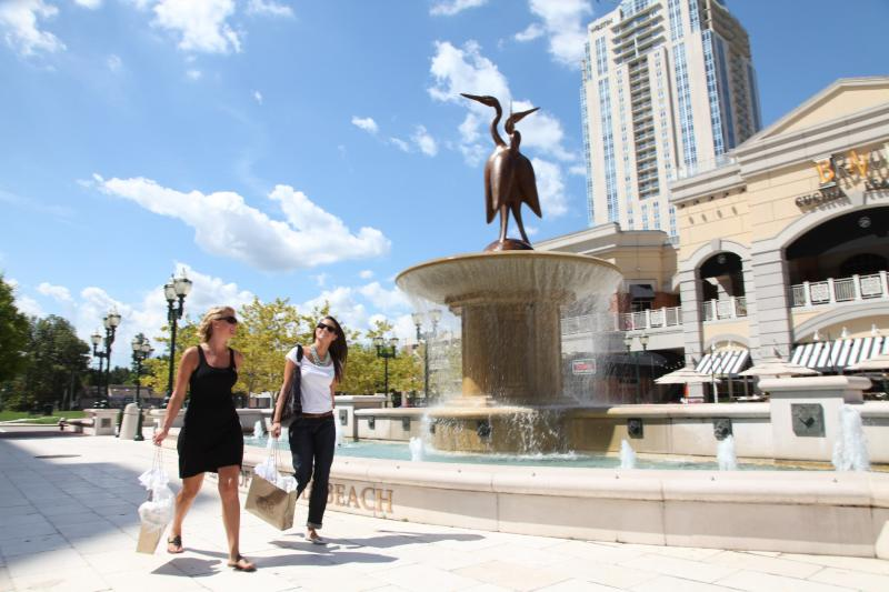 Two visitors stroll past a Town Center water fountain in Virginia Beach.