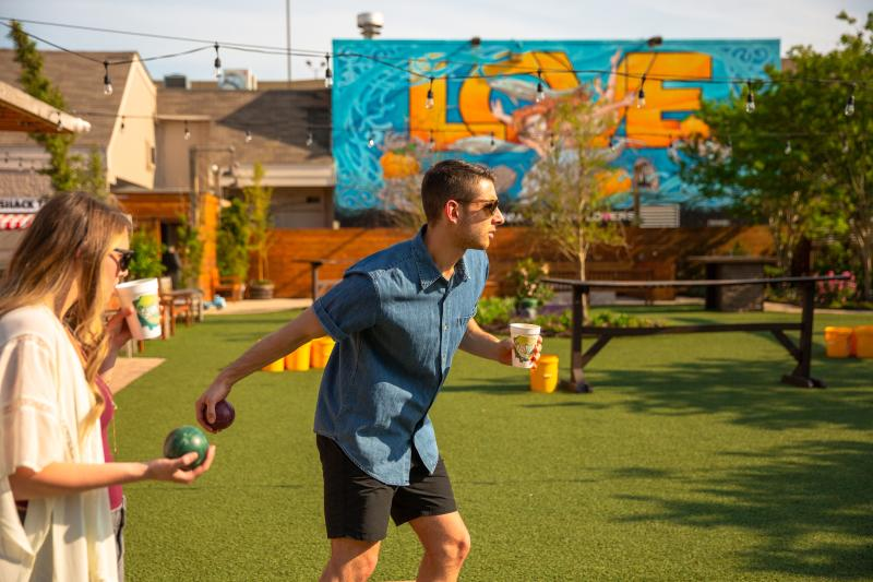Man and woman playing bocce ball at The Shack on 8th