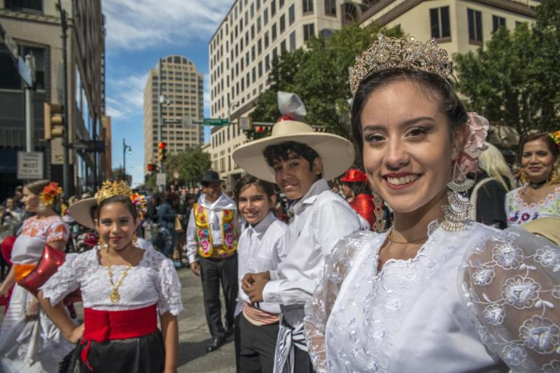 Young people dressed in traditional wear for Viva la Vida Parade during dia de los muertos celebrations in austin texas