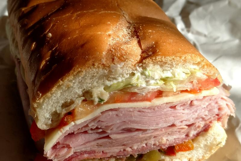 Close up of a sub sandwhich stacked with meat cuts, lettuce, tomato, and provolone between crispy Italian bread.