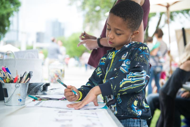 Child making a craft at Art City Austin festival