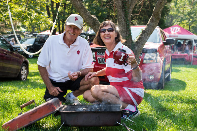 Man and woman tailgating in front of a grill holding an IU cup