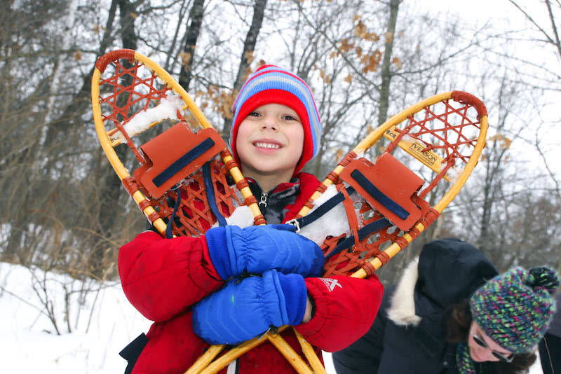 A boy posing with his snowshoe equipment at Beaver Creek Reserve