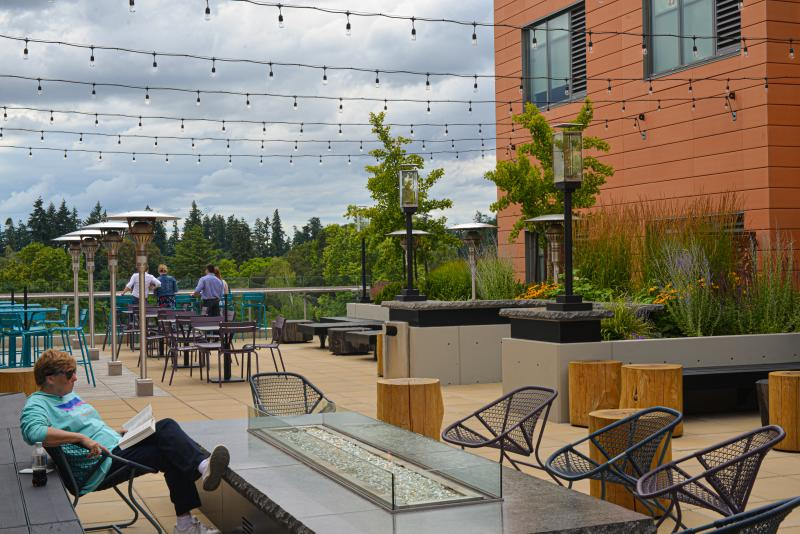 Person reads beside the fire pit on the sky deck lounge at Hyatt Place in Eugene. There are string lights, tables and people in suits drinking on the ledge in the distance.