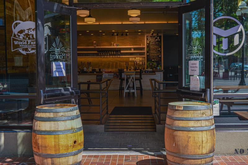 Two wine barrels sit in front of open doors leading into a clean looking taproom at Manifest Brewing.