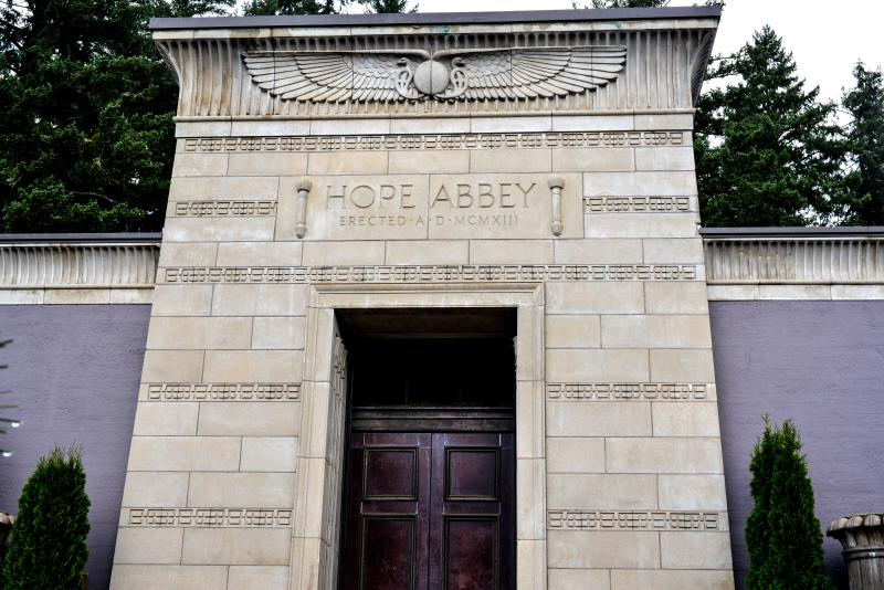 "Mausoleum with a large wooden door, details of a large winged scarab and the words ""Hope Abbey"" at Eugene Masonic Cemetery."