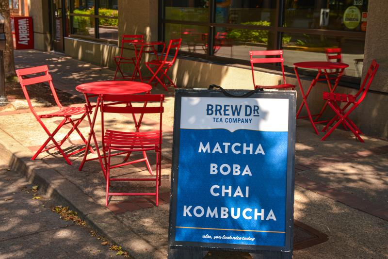 "A sign that says ""Brew Dr. Tea Company- Matcha, Boba, Chai and Kombucha"" sits in front of red outdoor dining tables with matching chairs."