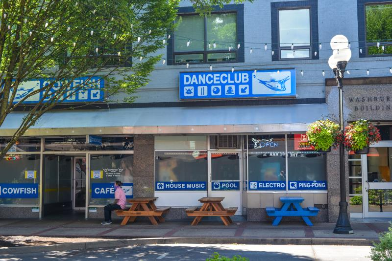 "Building with two large signs that say ""Cowfish Danceclub"" with outdoor tables in front of the building. This photo was taken across the street and string lights overhead. One masked person sits at one of the tables talking to someone out of frame. Photo by Melanie Griffin"