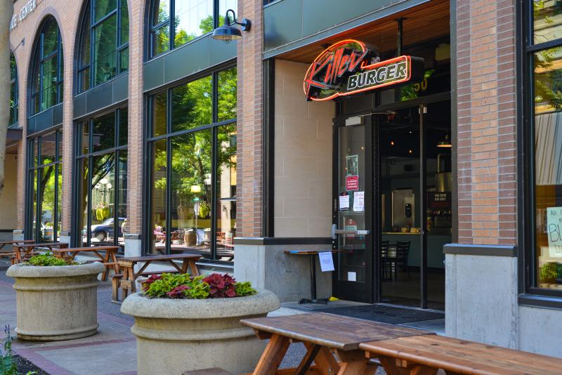 Large flower pots and outdoor dining tables in front of Killer Burger neon sign. Photo by Melanie Griffin