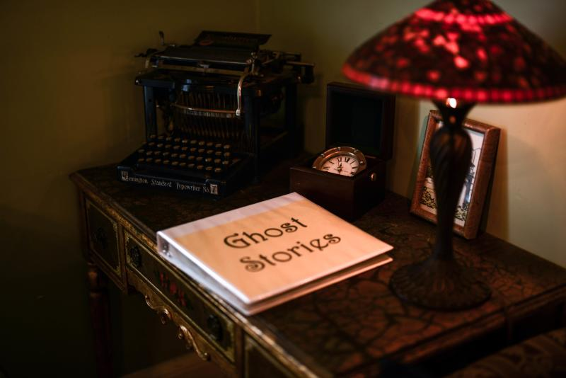 "An album titled ""Ghost Stories"" sits on a table beside a small red lamp and an antique typewriter at the Heceta Head Lighthouse Bed and Breakfast"
