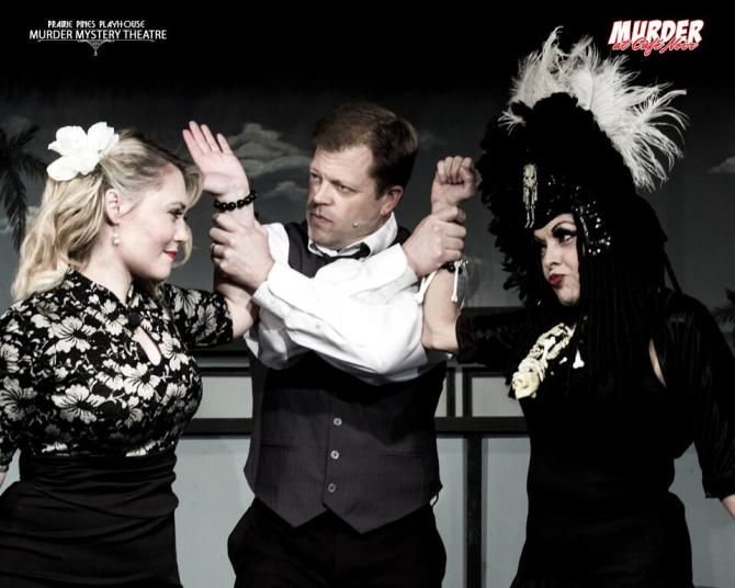 A man holds the arms a 2 women in a murder mystery performance