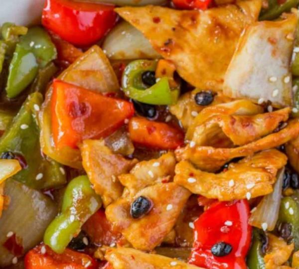 A dish of black bean chicken is mixed with red and green bell peppers.