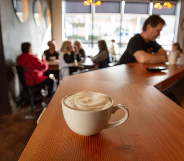 Foamy latte sitting on a coffee bar