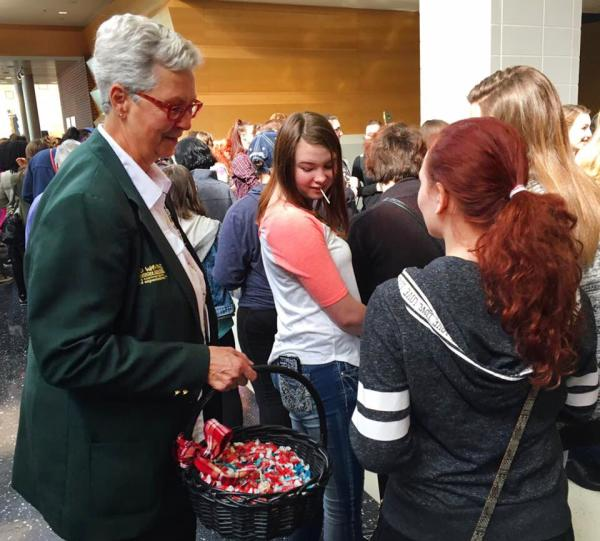 A Grand Wayne Convention Center host offers candy to event attendees