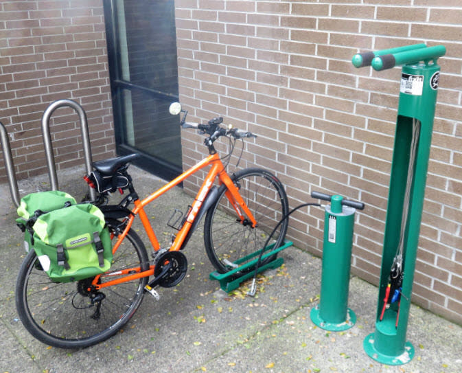 A bicycle at the bike repair station at the Sonoma Library, which has a green pump and a rack for working on your bike. There are bike tools hanging off of the rack.