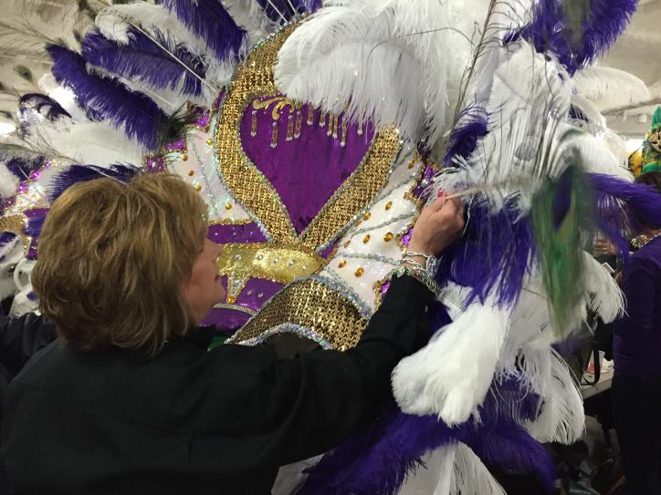 Krewe member attaching feather to Mardi Gras costume at Royal Gala.