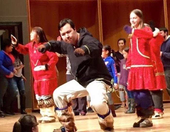 An Inupiaq dancer on stage in a concert hall