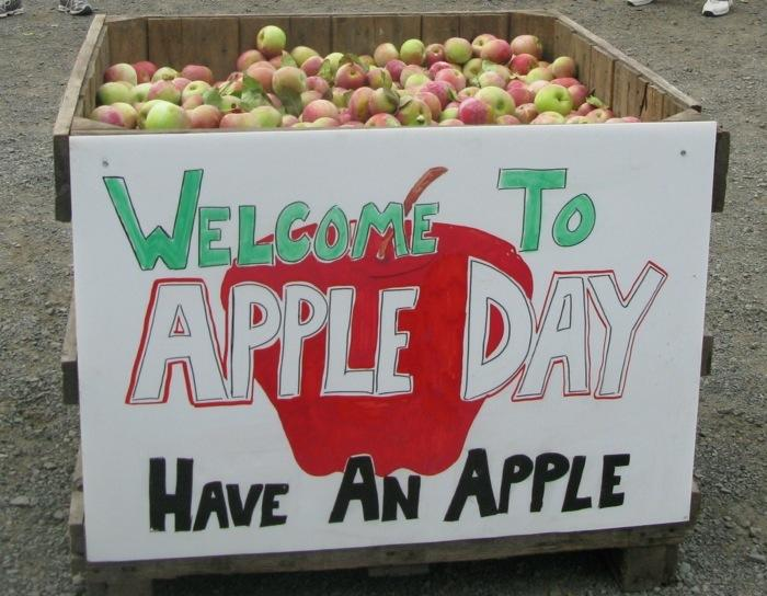 A bin of apples with a sign reading Welcome to Apple Day, Have an Apple