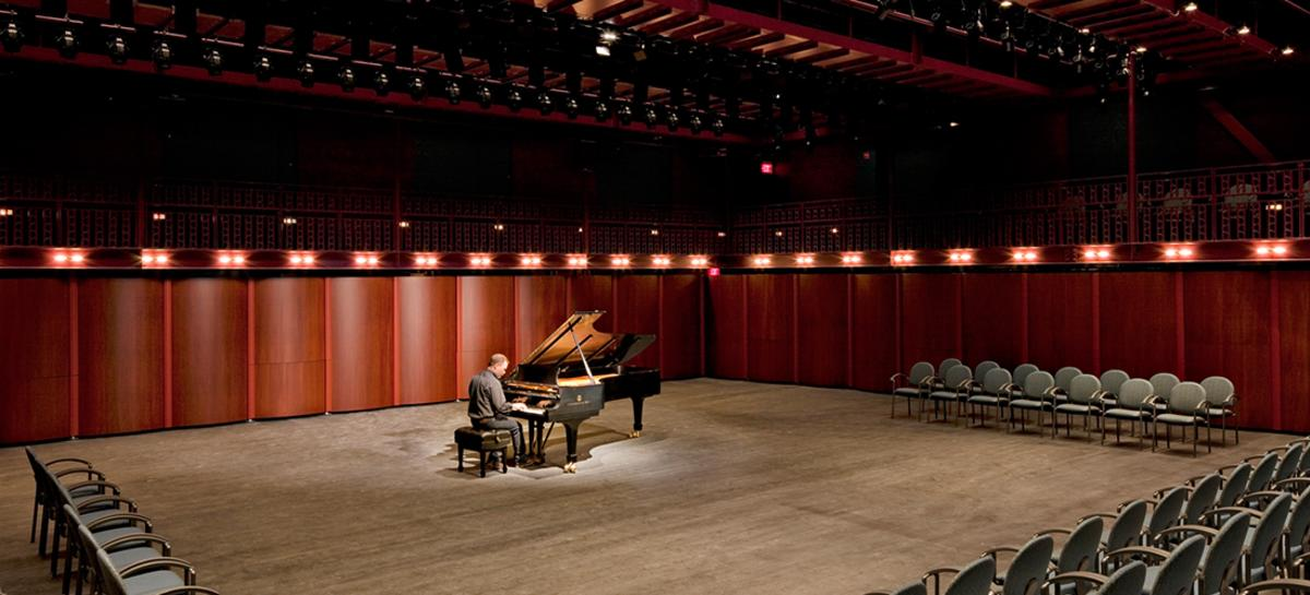 man playing piano in the empty Gregory Family Theater